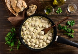 Delicious homemade swedish meatballs with creamy white sauce in frying pan over wooden background. Top view, lat lay, close up