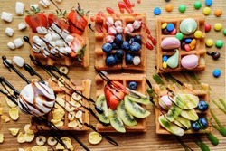 Delicious homemade waffles with  fresh fruits, ice cream, kiwi, meringue, strawberry, marshmallow, blueberry, colorful candy, different toppings, banana, jam  - sweet food