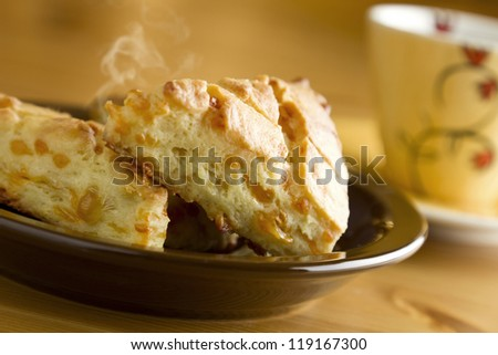 Delicious hot baked cheese biscuits on plate with cup of coffee.