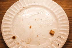 Delicious hot cinnamon roll with icing remnants on a dirty plate