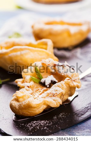 Delicious hot dessert: baked pears in pastry on rustic wooden background. Selective focus