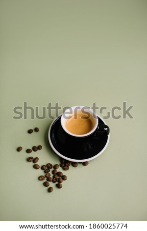 Delicious hot espresso with a beautiful thick crema in a ceramic black cup with a saucer standing on the green background Foto d'archivio ©