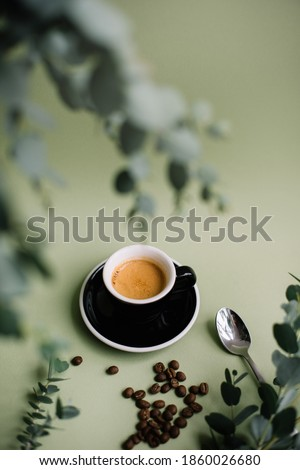 Delicious hot espresso with a beautiful thick crema in a ceramic black cup with a saucer standing on the green background, decorated with coffee beans and some fresh eucalyptus  Foto d'archivio ©