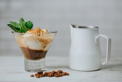 Delicious iced caramel coffee latte with cream and ice cream in a glass. White milk pitcher - frothing jug, fresh mint leaves and coffee beans decoration. White table. Selective focus.