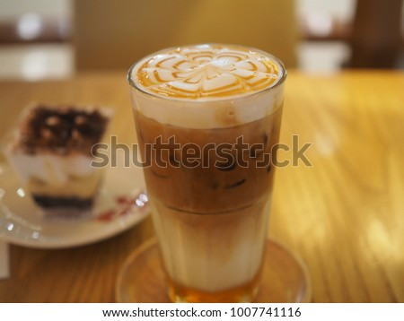 Delicious iced caramel coffee with milk foam serve with banana cream cake #1007741116