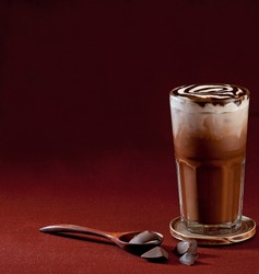 Delicious iced mocha or chocolate frappe espresso and chocolate topping foam on red linen texture background for menu illustration design bar restaurant edition square format
