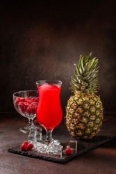 Delicious icy cocktail with fruits on dark grounge background. Healthy colorfull fruit shakes with ice on textured table.