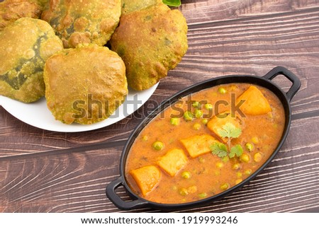 Delicious Indian Palak Poori Or Paalak Puri Made Of Wheat Flour Gehoon Ka Aata Mixed With Blenched Spinach Leaves Served With Alu Matar Sabzi Or Veg Curry Sabji. Wooden Background With Copy Space Foto stock ©