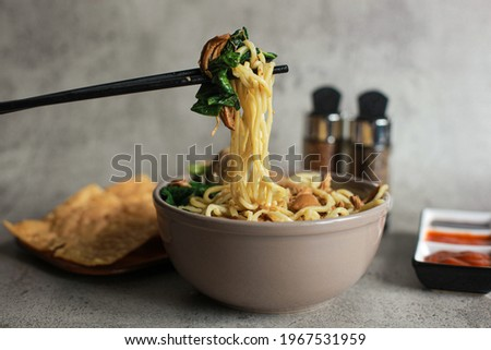 Delicious Indonesian chicken noodles called mie ayam topped with chicken meat and green vegetable served in a bowl or plate with wooden chopsticks Zdjęcia stock ©