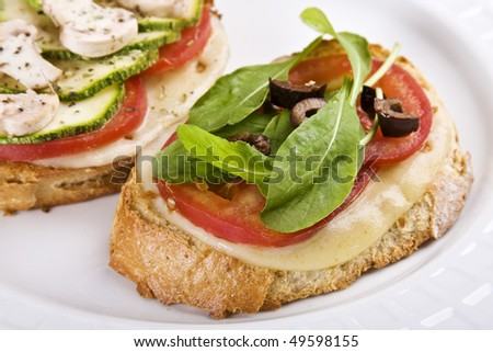 Delicious Italian bruschetta made with mozzarela cheese, tomatoes, arugula, black olives, zucchini and mushrooms on a toasted country bread. - stock photo
