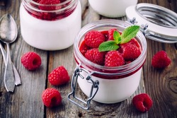 Delicious italian dessert panna cotta with raspberry sauce, fresh berries and mint on wooden background