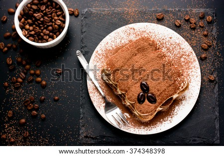 Delicious Italian dessert tiramisu with chocolate, cocoa and coffee beans on a black background. Top view with copy space
