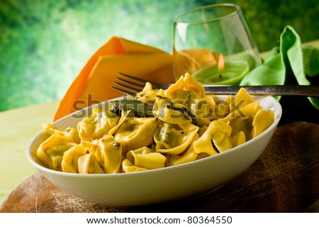 delicious italian fresh tortellini with butter and sage with green background