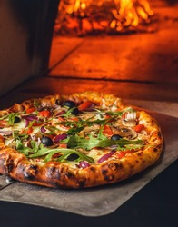 Delicious Italian pizza in a shovel putting in wood burning oven