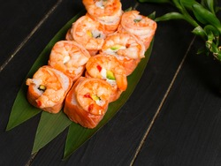 Delicious Japanese seafood sushi roll with salmon tataki and roasted black tiger shrimps on top served on bamboo leaves with bamboo plant on black wooden background