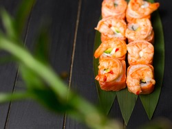 Delicious Japanese sushi roll with salmon tataki and roasted black tiger shrimps on top served on bamboo leaves with bamboo plant out of focus on foreground. inside out seafood roll