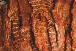 delicious jerky on a wooden background. products in craft packaging. snack for alcohol. macro photo. close-up