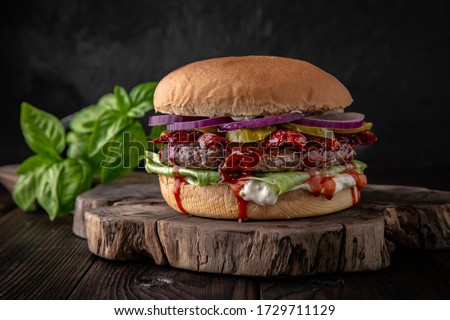 Delicious juicy burger from Brioche Bun, Steak New York, American Cheddar, Sun-dried tomatoes, Red onion, Onion marmalade, Iceberg. Hamburger for poster or menu.
