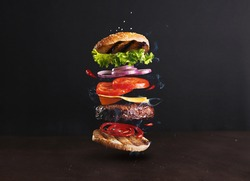 Delicious, juicy burger layers over a dark background