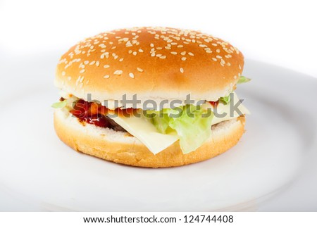 Delicious juicy cheeseburger with tomato and lettuce on a plate on white background