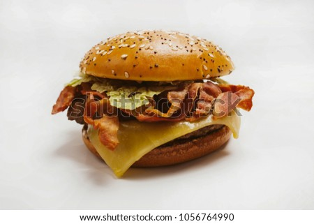 Delicious juicy hamburger isolated on white background. hamburger with sesame seeds, poppy seeds, chop, fried bacon, greens, cheese isolated on white background. Close-up. vintage photo processing