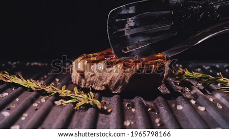 Delicious juicy meat steak cooking on grill. Kitchen tongs. Aged prime rare roast grilling tenderloin fresh marble tenderness beef. Prime beef fry on electric roaster, rosemary black pepper, salt. Stockfoto ©