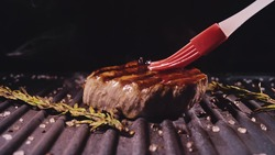 Delicious juicy meat steak cooking on grill. Silicone cooking brush. Aged prime rare roast grilling fresh marble tenderness beef. Prime beef fry on electric roaster, rosemary black pepper oil.