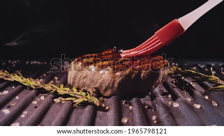 Delicious juicy meat steak cooking on grill. Silicone cooking brush. Aged prime rare roast grilling fresh marble tenderness beef. Prime beef fry on electric roaster, rosemary black pepper oil. Stock photo ©
