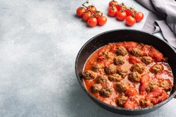 Delicious juicy Meatballs in tomato sauce are cooked in a castiron pan. Concrete background. Copy space.