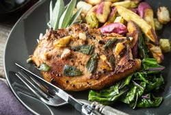 Delicious juicy pork chop with sage, garlic and root vegetables