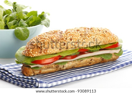 Delicious large submarine sandwich with ham, lettuce, tomatoes and cucumbers on white background