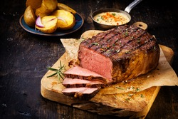 Delicious lean rare roast beef seasoned with fresh herbs and rosemary and carved ready to serve with golden roast potatoes