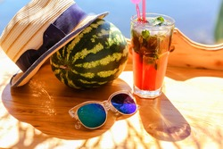 Delicious lemonade in glass on table against background of sea on vacation.Cold fruit drink juice in hot summer at resort.Sunglasses.Sweet watermelon.Straw hat.Alcoholic cocktail at beach bar