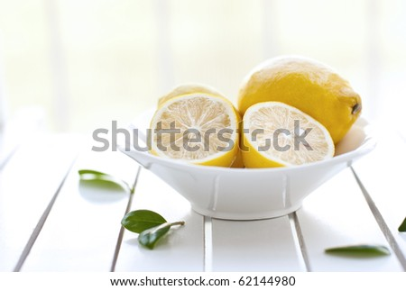 Delicious lemons in a bowl on garden table