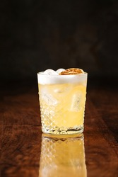 delicious light yellow sour foam cocktail in the etched glass with ice and dried lemon slice, dark wooden background, vertical, side view