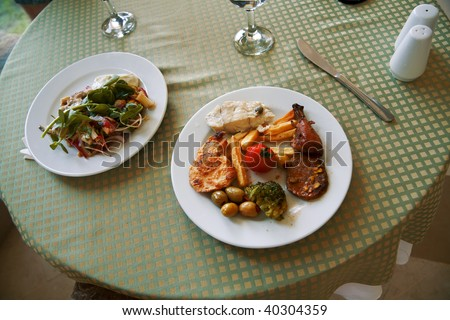 delicious meat and vegetable dishes on the table of restaurant