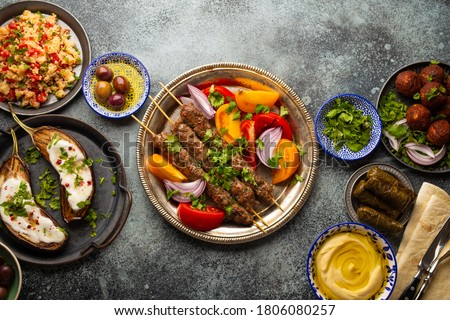 Delicious meat kebab with fresh vegetable salad served with variety of Middle eastern dishes and appetizers. Top view of assorted Arab food and meze, tasty and healthy Mediterranean cuisine