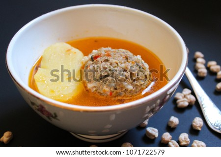 Delicious meatballs in sauce with potatoes. Close up, black background. National azeri food Kufte