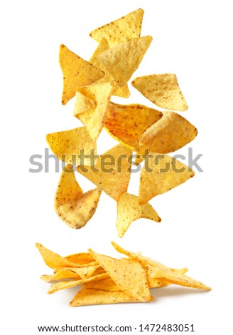 Delicious Mexican nachos chips falling into pile on white background Foto stock ©
