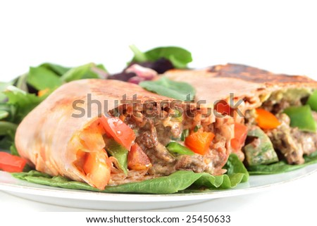 delicious mexican steak burrito with fresh vegetables - stock photo