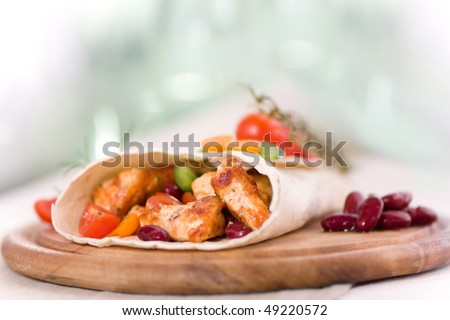 Delicious mexican wrap with chicken stripes and vegetable