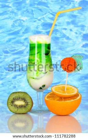 Delicious milk shake with fruit on blue sea background