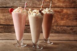Delicious milkshakes on wooden background