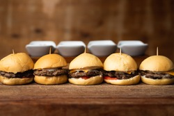 Delicious mini burgers as snacks with cheddar cheese, tomato and mayonnaise, put in line on a wooden table and a raw background. Horizontal image with space for text.
