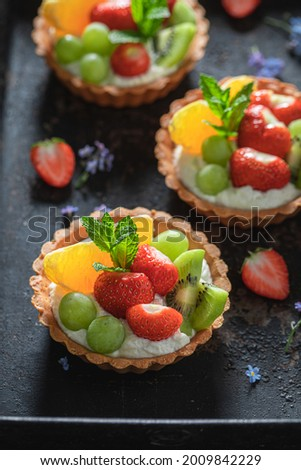 Delicious mini tart with various fruits. Sweet summer dessert. Tart with cream and fruit.
