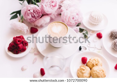 Delicious morning breakfast table essentials: fresh cappuccino coffee, marshmallow, cookies, chocolate, red raspberries, glass of water and tender pink blossoming peony bouquet on the white background