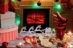 Delicious mulled wine, Christmas decorations and gift boxes on the table. Christmas burning fireplace in blurred background.