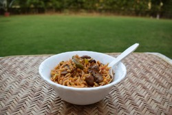 Delicious Mushroom fried rice with babycorns and other vegetables. Indian food cuisine like Mushroom biryani or pulav served in white bowl on table with outdoor background