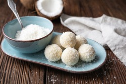 Delicious no bake candy, white chocolate truffles covered in shredded coconut on rustic wooden background