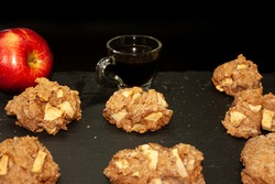 Delicious oatmeal cookies with natural apple cubes, arranged on black slate stone gourmet kitchen to accompany the morning black coffee